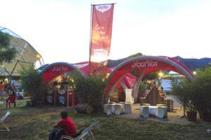 To oppblåsbare telt med Yogi Tea logo på en festival